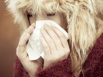 Donna malata che starnutisce nel tessuto all'aperto Fotografia Stock Libera da Diritti