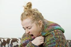 Donna malata con l'emicrania che si siede sotto la coperta immagini stock