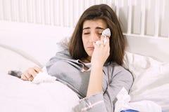 Donna malata a letto che tiene fazzoletto Fotografia Stock Libera da Diritti