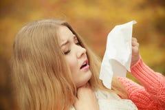 Donna malata malata nel parco di autunno che starnutisce nel tessuto Fotografia Stock Libera da Diritti