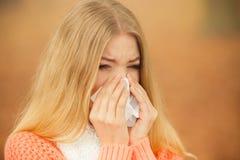 Donna malata malata nel parco di autunno che starnutisce nel tessuto Fotografie Stock