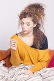 Donna malata povera, prendente la sua temperatura con un termometro Fotografia Stock