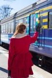 Donna in mano d'ondeggiamento rossa sulla piattaforma fotografie stock