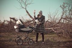 Donna in maschera antigas con il Buggy di bambino immagine stock libera da diritti