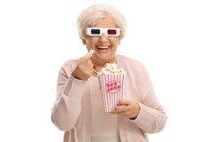 Donna matura allegra con i vetri 3D che mangiano popcorn Immagine Stock