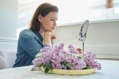 Donna matura 40 anni che esaminano il suo fronte nello specchio, seduta femminile alla tavola a casa che fa trucco immagini stock