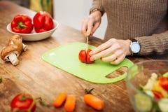 Donna matura attenta con l'orologio sul suo polso che taglia le verdure fotografia stock