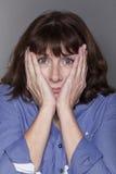 Donna matura attraente ansiosa che nasconde il suo fronte Immagini Stock Libere da Diritti