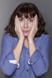 Donna matura attraente ansiosa che nasconde le sue guance Fotografie Stock Libere da Diritti