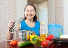 Donna matura che cucina con le verdure Fotografia Stock