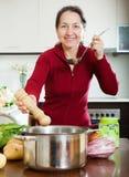 Donna matura che cucina minestra nella sua cucina Fotografia Stock