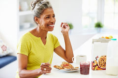 Donna matura che mangia prima colazione a casa Immagini Stock