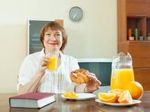 Donna matura che mangia prima colazione con il libro Fotografie Stock