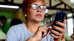 Donna matura che muove il contenuto dello schermo verso l'alto Internet dello Smart Phone che passa in rassegna video d archivio