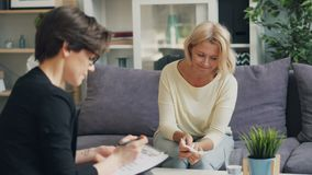 Donna matura che parla con psicologo femminile che si siede sullo strato in ufficio moderno archivi video