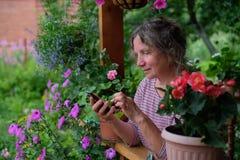 Donna matura che rivolge al telefono e che esamina i fiori Fotografie Stock Libere da Diritti