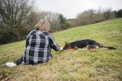 Donna matura che si siede all'aperto con un cucciolo alsaziano Immagini Stock