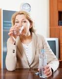 Donna matura che si siede nella tavola e nell'acqua dolce bevente Immagine Stock