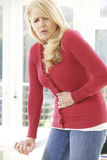 Donna matura che soffre dal mal di stomaco a casa Immagine Stock