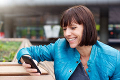 Donna matura che sorride e che esamina telefono cellulare Fotografie Stock Libere da Diritti