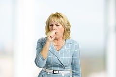 Donna matura che tossisce nella sua mano Fotografia Stock