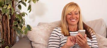Donna matura che usando Smartphone Fotografia Stock Libera da Diritti