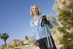 Donna matura con Pali di camminata fotografie stock libere da diritti