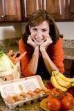 Donna matura in cucina con gli ingredienti freschi fotografia stock libera da diritti