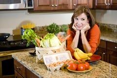 Donna matura in cucina con gli ingredienti freschi immagini stock