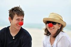 Donna matura divertendosi con il figlio cresciuto sulla festa della spiaggia Fotografia Stock Libera da Diritti