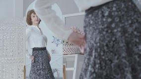Donna matura elegante graziosa che guarda nello specchio, esaminante la sua riflessione La signora che esamina la sua nuova gonna archivi video