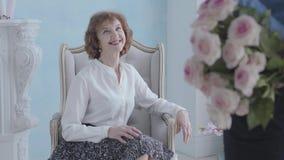 Donna matura elegante incantante in blusa bianca che si siede nel sorridere della poltrona L'uomo irriconoscibile che sta con il  video d archivio