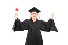 Donna matura estatica che tiene un diploma Fotografia Stock