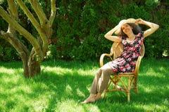 Donna matura felice che si siede in un giardino Fotografia Stock Libera da Diritti