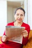 Donna matura in giornale rosso della lettura Immagine Stock Libera da Diritti