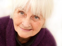 Donna matura più anziana amichevole su priorità bassa bianca Fotografie Stock Libere da Diritti