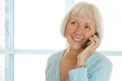 Donna matura sorridente che comunica sul telefono delle cellule Fotografie Stock Libere da Diritti