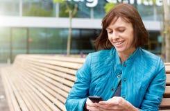 Donna matura sorridente che per mezzo del telefono cellulare fuori Fotografia Stock