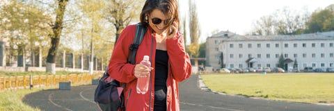 Donna matura sportiva allo stadio, insegna panoramica del ritratto, in vestiti di sport per la formazione, con la bottiglia di ac immagine stock libera da diritti
