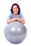 Donna matura sportiva felice che si siede con la palla di forma fisica isolata sopra fotografia stock libera da diritti
