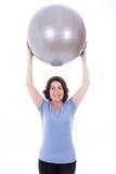 Donna matura sportiva felice con la palla di forma fisica isolata su bianco immagine stock