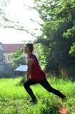 Donna media in buona salute che fa allungamento di forma fisica Immagini Stock