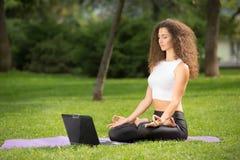 Donna Meditating con il computer portatile Fotografia Stock