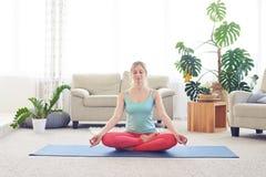 Donna meravigliosa che medita nel asana del loto su stuoia di yoga Fotografia Stock Libera da Diritti
