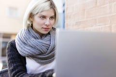 Donna messa a fuoco che lavora con il computer portatile all'aperto al caffè Fotografia Stock Libera da Diritti