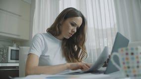 Donna messa a fuoco di affari che lavora con le carte a casa Documenti di lavoro della donna video d archivio