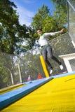 Donna in mid-air sul trampolino fotografia stock