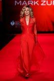 Donna Mills anda a pista de decolagem no vermelho ir para a coleção vermelha 2015 do vestido das mulheres Imagens de Stock