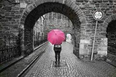 Donna misteriosa dietro un ombrello in bianco e nero di rosa del colorsplash dell'ombrello Fotografie Stock