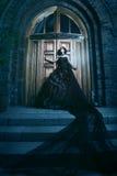 Donna misteriosa in vestito nero vicino alla chiesa fotografie stock libere da diritti